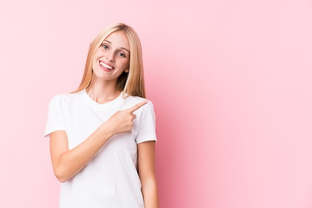 Young blonde woman on pink wall smiling and pointing aside, showing something at blank space.