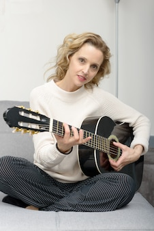 Young blonde woman playing the acoustic guitar