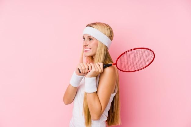 Молодая блондинка играет в бадминтон изолированы