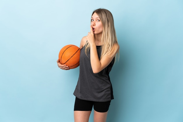 Young blonde woman playing basketball isolated on blue wall doing silence gesture