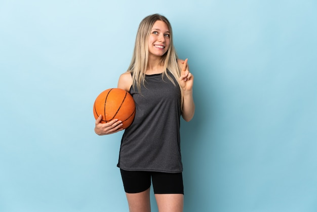 Young blonde woman playing basketball isolated on blue wall with fingers crossing