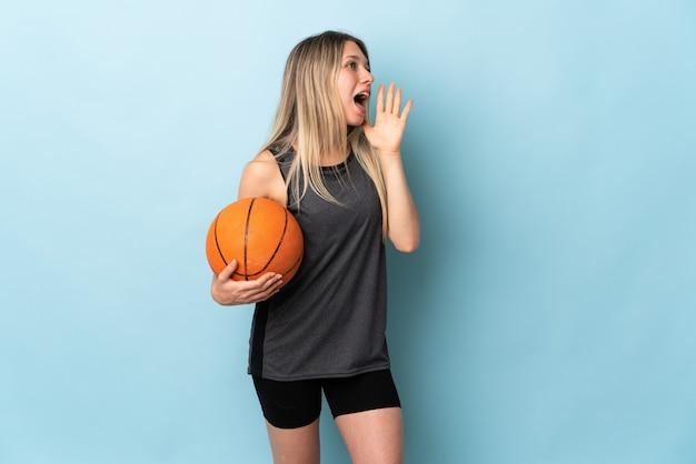 Молодая блондинка играет в баскетбол изолирована на синей стене и кричит с широко открытым ртом