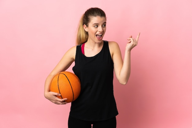 Young blonde woman playing basketball isolated on pink background intending to realizes the solution while lifting a finger up