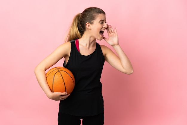 Young blonde woman playing basketball isolated on pink background shouting with mouth wide open to the side
