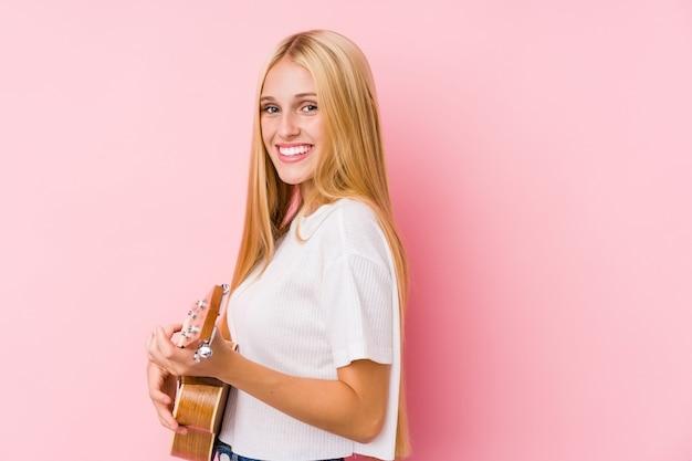 Молодая блондинка играет на укелеле, изолированном в стене