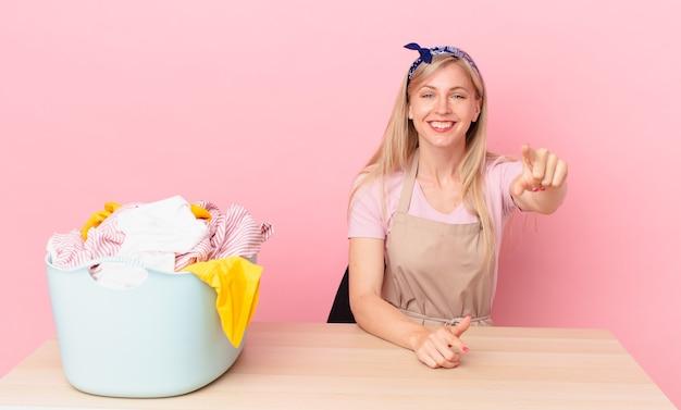 Молодая блондинка женщина, указывая на камеру, выбирая вас. концепция стирки одежды