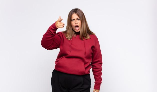 猛烈な、狂った上司のように見える怒っている攻撃的な表情でカメラを指している若いブロンドの女性