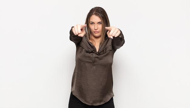 指と怒りの表情でカメラを前に向けて、あなたに義務を果たすように言っている若いブロンドの女性