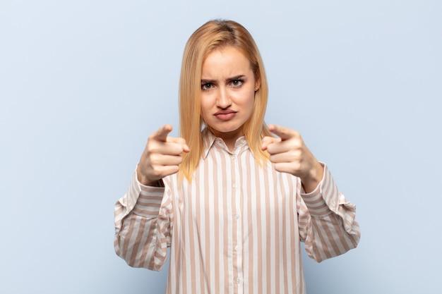 指と怒りの表情の両方で前を向いて、あなたにあなたの義務を果たすように言っている若いブロンドの女性
