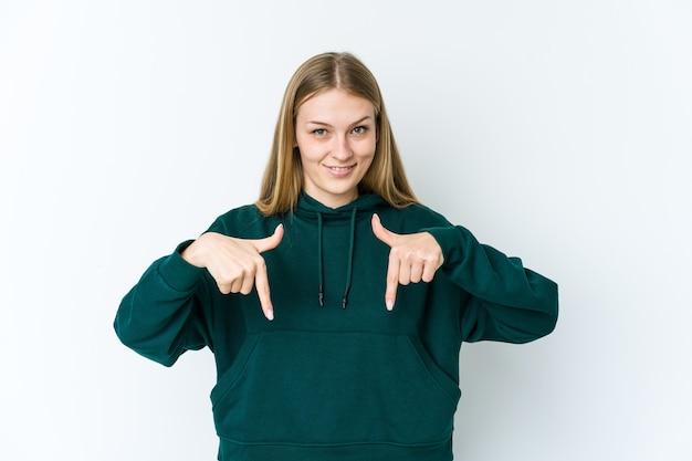 Молодая блондинка указывает пальцами вниз, положительное чувство.