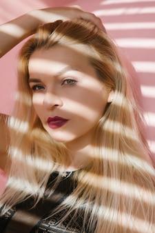 젊은 금발의 여자 초상화입니다. 여성 패션 모델. 블라인드 그림자 효과.
