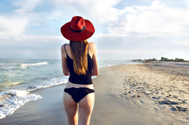 Young blonde woman posing back and walking alone near ocean, lonely beach, slim bode, wearing black bikini and elegant red hat, amazing nature view, travel on the beach.