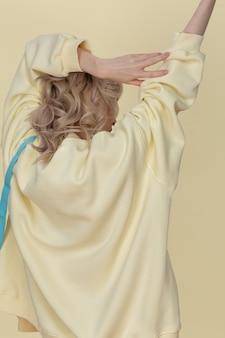 カメラに戻って黄色のスウェットシャツでポーズをとって若いブロンドの女性