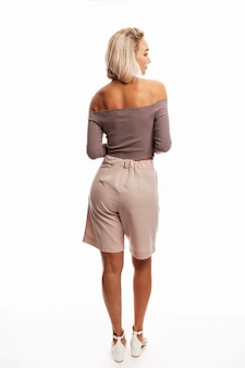 A young blonde woman posing on white. back view