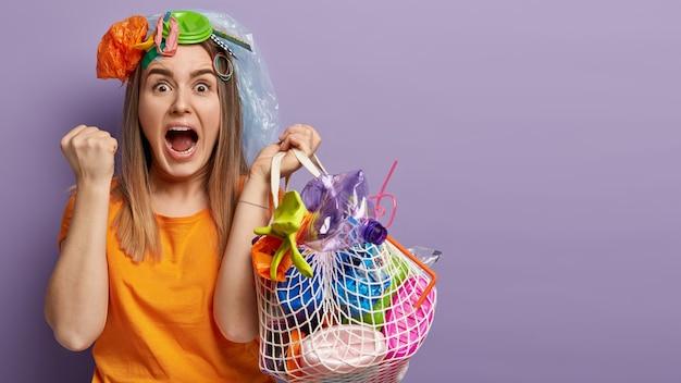 Молодая блондинка позирует с пластиковыми отходами