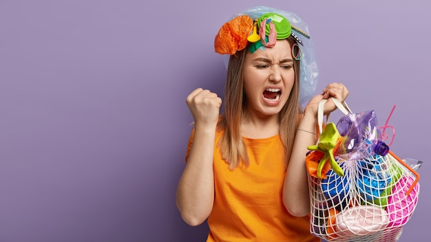 Giovane donna bionda in posa con i rifiuti di plastica
