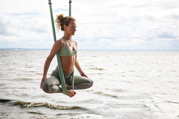 Young blonde woman practicing aerial yoga in silk hammock on the beach. professional trainer make stretching exercise in antigravity fly yoga outdoors by the sea. wellness and healthy concept. Premium Photo