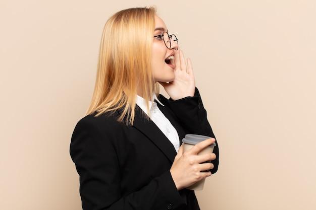젊은 금발의 여성 프로필 보기, 행복하고 흥분된 모습, 소리를 지르며 옆에 공간을 복사하기 위해 전화