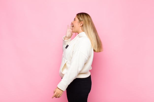 Young blonde woman profile view, looking happy and excited, shouting and calling to copy space on the side against flat wall