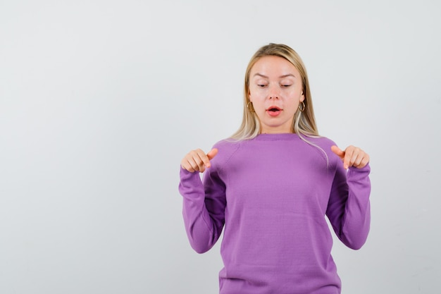 Young blonde woman in a purple sweater