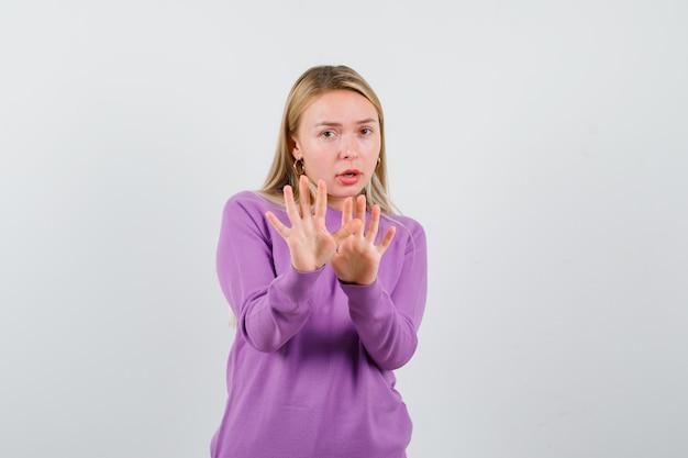 Giovane donna bionda con un maglione viola