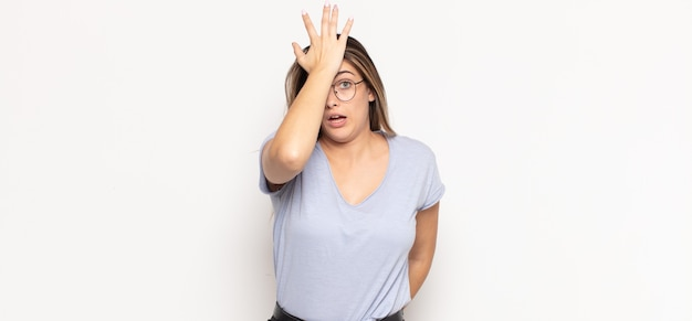 Young blonde woman raising palm to forehead thinking oops, after making a stupid mistake or remembering, feeling dumb