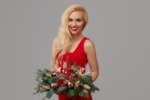 A young blonde woman in a red dress holds a christmas wreath in her hands. festive bouquet of flowers and christmas tree branches on a gray neutral background