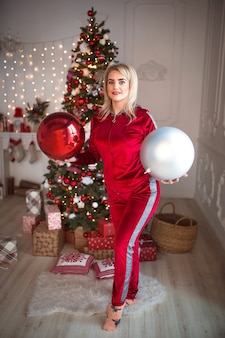 Young blonde woman in a red tracksuit on christmas decorations