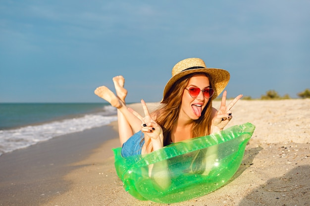 Young blonde woman relax and enjoy her summer vacation, lay on air mattress and getting sunbathe, bright stylish beachwear hat and sunglasses