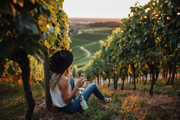 Young blonde woman relaxing in the vineyards in the summer season with a bottle of wine