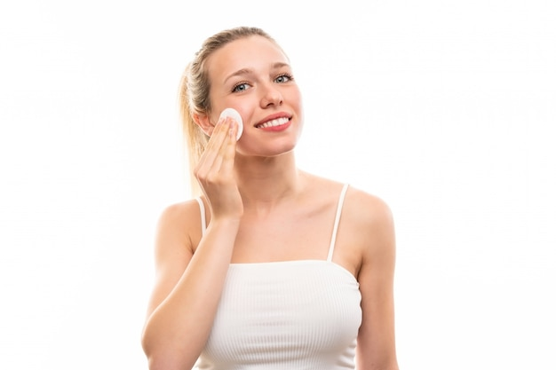 Young blonde woman removing makeup from her face with cotton pad
