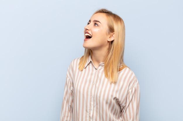 若い金髪の女性が猛烈に叫び、積極的に叫び、ストレスを感じて怒っているように見える