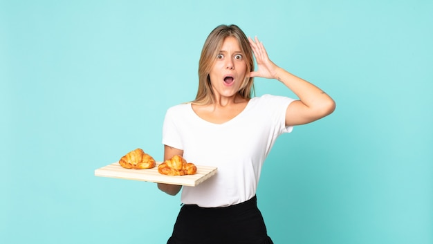 Young blonde woman screaming with hands up in the air and holding a croissant tray