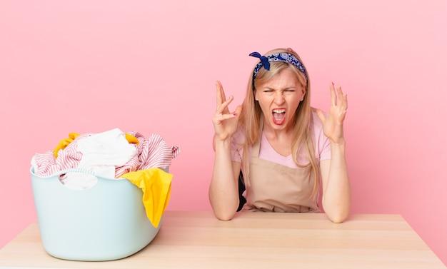 Молодая блондинка кричала с поднятыми руками в воздухе. концепция стирки одежды