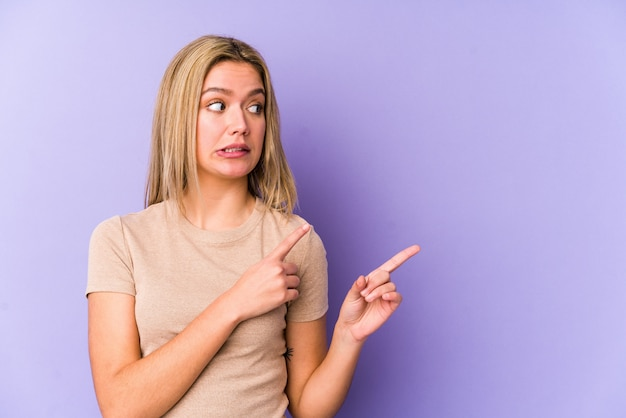 Young blonde woman shocked pointing with index fingers