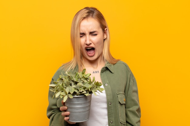 Young blonde woman shouting aggressively, looking very angry, frustrated, outraged or annoyed, screaming no