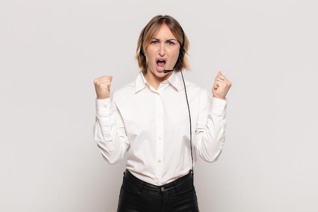 怒りの表情や成功を祝って握りこぶしで積極的に叫ぶ若いブロンドの女性