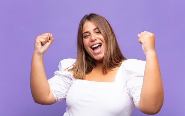 흥분, 행복하고 놀란 승자처럼 보이는 젊은 금발의 여인이 승리를 거두었습니다.