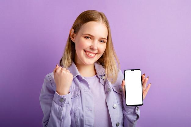 젊은 금발 여성은 고립된 보라색 배경 위에 빈 스마트폰 화면 모형을 보여줍니다.