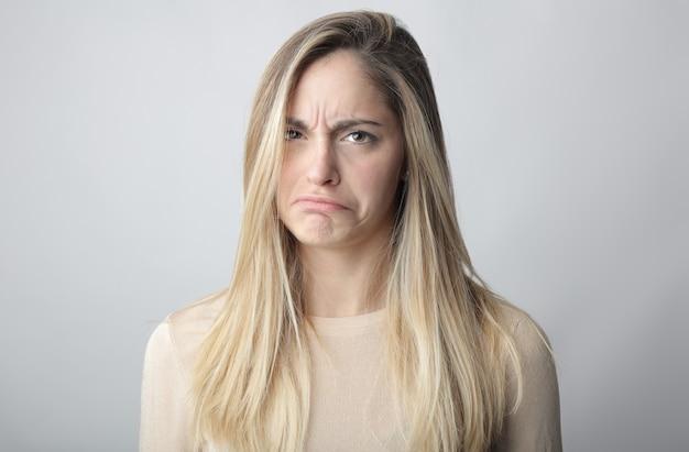 Giovane donna bionda che mostra un volto di incertezza e dubbio