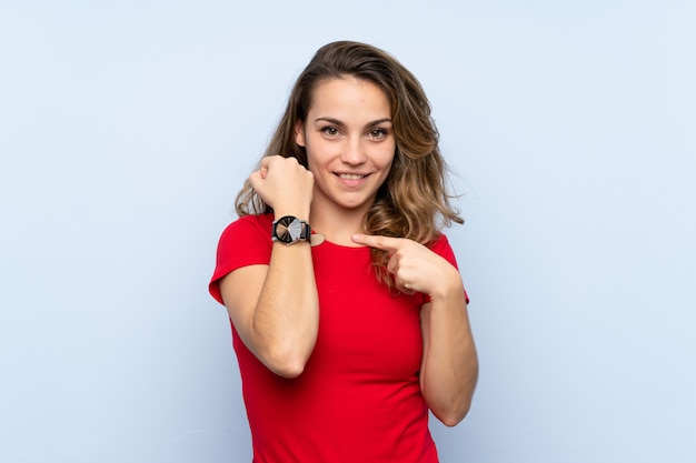 Young blonde woman showing the hand watch
