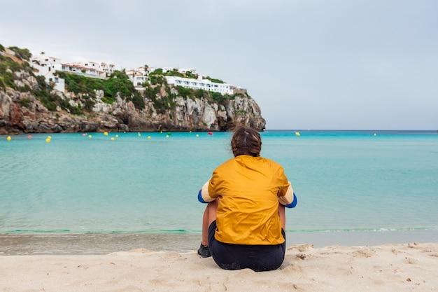 Молодая блондинка женщина сидит на спине, глядя на море