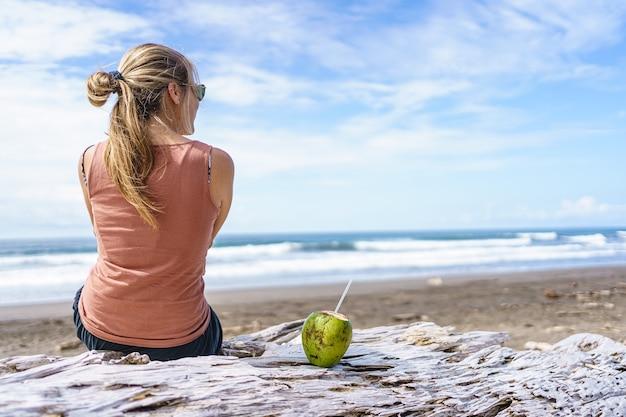 Молодая блондинка женщина сидит на пляже с открытым кокосом с соломинкой. пляж хако в коста-рике