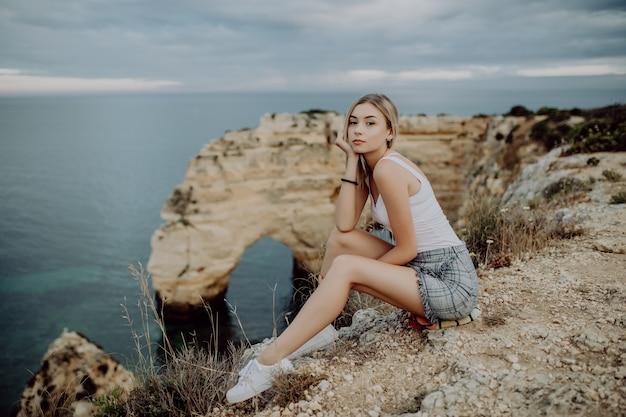 Молодая блондинка женщина, сидящая на вершине скал у океана.