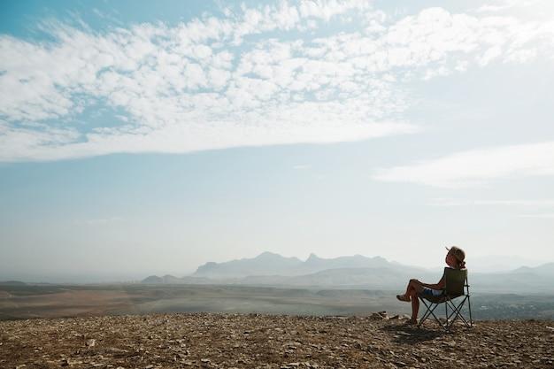 Молодая блондинка женщина сидит на вершине холма