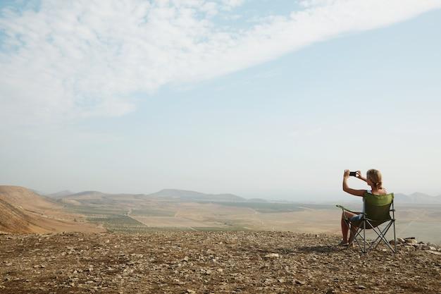 丘の上に座っている若いブロンドの女性