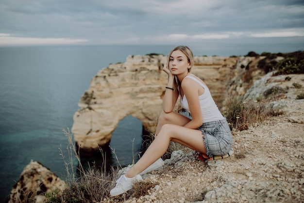 Young blonde woman sitting on the rocks top by the ocean.