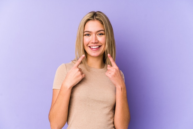 Young blonde woman smiles, pointing fingers at mouth