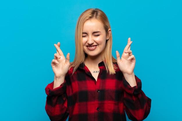 Молодая блондинка улыбается и тревожно скрещивает пальцы, чувствуя беспокойство и желая или надеясь на удачу