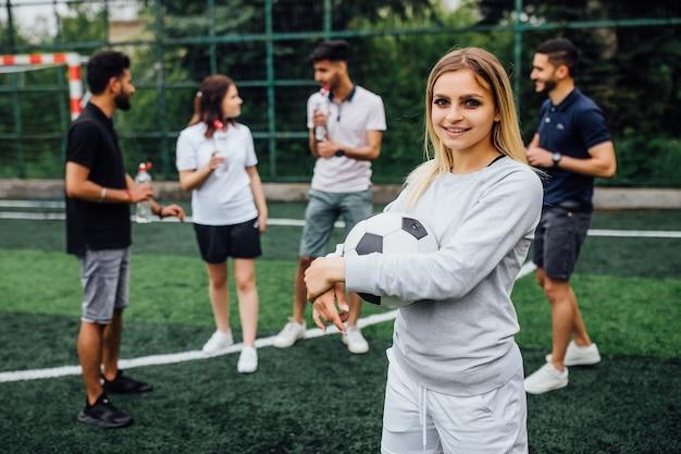 笑顔で幸せな、サッカーボールを持って、ゲームをプレイすることに興奮している若い金髪の女性